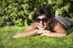 Beautiful woman lying down on a fresh green grass. Beautiful smiling woman lying down on a fresh green grass royalty free stock photo