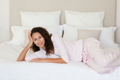 Beautiful woman lying down on her bed Royalty Free Stock Photography