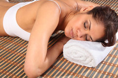 Beautiful woman lying face down in spa on towel Royalty Free Stock Photography