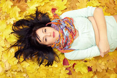 Beautiful woman lying in fallen leaves. Wearing colourful scarf Royalty Free Stock Photo