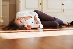 Beautiful woman lying on the floor at apartment Stock Photography
