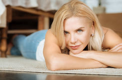 Beautiful woman lying on the floor in her bedroom Stock Image