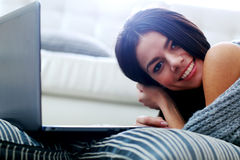 Beautiful woman lying on the floor with laptop Royalty Free Stock Image