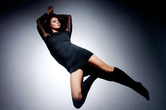Beautiful woman lying on floor in light circle Stock Photos