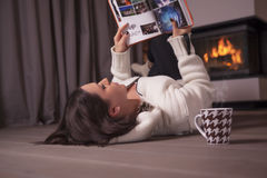 Beautiful woman lying on floor and reading book by fireplace Stock Photography