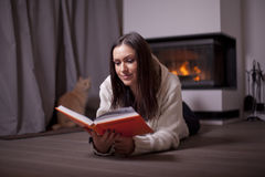 Beautiful woman lying on floor and reading book by fireplace Royalty Free Stock Photos