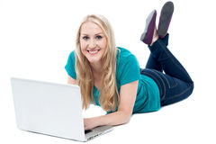 Beautiful woman lying on the floor, using laptop Stock Photos