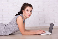 Beautiful woman lying on the floor and using laptop Royalty Free Stock Images