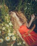 Beautiful woman lying in flowers Stock Photo