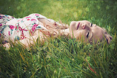 Beautiful woman lying in grass with her eyes closed. Royalty Free Stock Photography