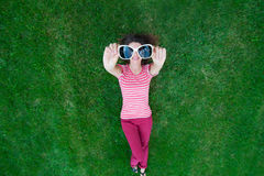 Beautiful woman lying on the grass and holding glasses in his hand Stock Photo