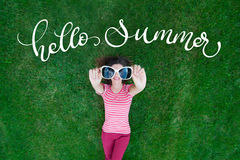 Beautiful woman lying on the grass and holding glasses in his hands. text Hello Summer. Calligraphy lettering Stock Photos