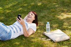 Beautiful woman lying in grass smiling with smart phone Stock Image