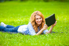 Beautiful woman lying in grass with tablet Stock Images