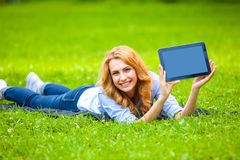 Beautiful woman lying in grass with tablet Royalty Free Stock Photos