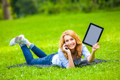 Beautiful woman lying in grass with tablet Stock Photography