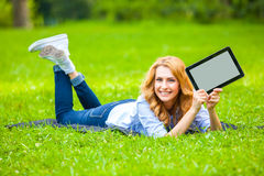 Beautiful woman lying in grass with tablet Royalty Free Stock Image