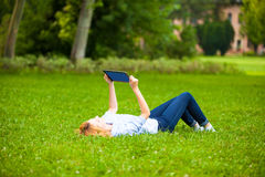 Beautiful woman lying in grass with tablet Stock Photo