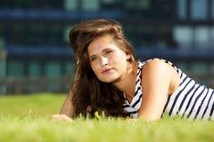 Beautiful woman lying on grass thinking Royalty Free Stock Photos