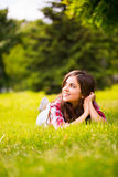 Beautiful woman lying on green grass Royalty Free Stock Photos