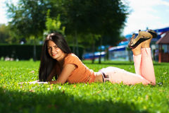 Beautiful woman is lying on green grass on sunny day in th Royalty Free Stock Photography