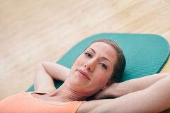 Beautiful woman while lying on gym floor Royalty Free Stock Photo