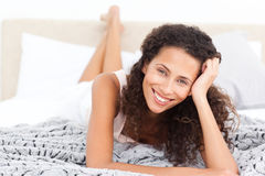 Beautiful woman lying on her bed Stock Photography