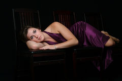 Beautiful Woman Lying on Her Side in a Purple Gown Stock Photography