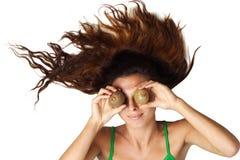 Beautiful woman lying and hold kiwi near eyes Stock Photos