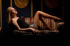Beautiful woman lying on a leather sofa Royalty Free Stock Photo