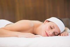 Beautiful woman lying on massage table at spa center Stock Photo