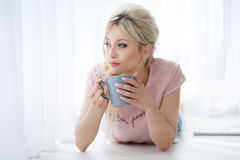 Beautiful Woman Lying On A White Floor With A Cup Of Tea Royalty Free Stock Photos