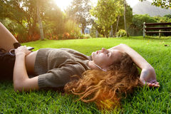 Beautiful woman lying outside listening to music Royalty Free Stock Image