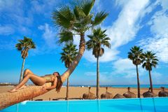 Woman lying on pool bent palm tree trunk Stock Photo