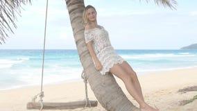 Beautiful woman lying on palm tree by the sea. Slow motion. Beautiful woman lying on palm tree by the sea. Slow motion stock footage