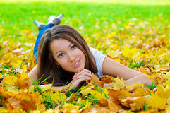 Beautiful woman lying in the park. Young beautiful woman lying in the autumn park stock image