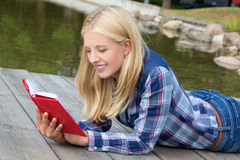 Beautiful woman lying in park and reading book Stock Images