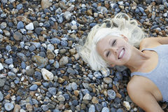 Beautiful Woman Lying On Pebbles At Beach. High angle portrait of beautiful young woman lying on pebbles at beach Stock Image