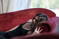 Beautiful woman lying on red couch Stock Image