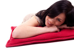 Beautiful woman lying on the red pillow Stock Images