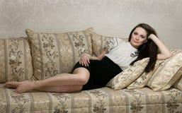 Beautiful woman lying on sofa stock photos
