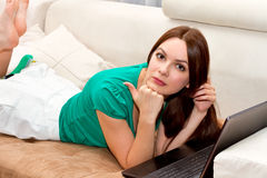 Beautiful woman lying on the sofa. With laptop Stock Photography