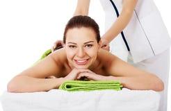 Beautiful woman lying on spa salon having stone massage. Royalty Free Stock Photo