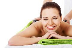 Beautiful woman lying on spa salon having stone massage. Royalty Free Stock Image