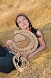Beautiful woman lying in the straw with the hat Stock Photography