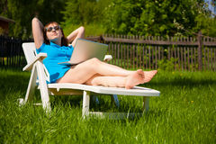 Woman lying in sun lounger and looking on laptop Stock Photography