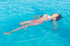 Beautiful woman lying on swimming pool water surface Stock Photo