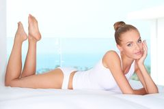 Beautiful woman lying on white bed Stock Photos