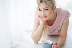 Beautiful woman lying on a white floor with a Cup of tea. Beautiful young woman with long blonde hair and blue eyes,light makeup and pink lipstick,wearing a pink Stock Photo