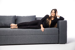 Beautiful woman lying on a white sofa, isolated on white Royalty Free Stock Photo